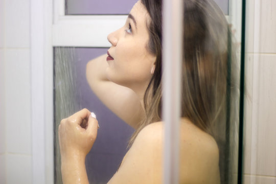 Beautiful woman in the shower behind glass with drops