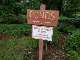 wood sign that says ponds and gate closed at 5pm