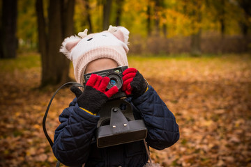 Little child with old retro camera doing photo outdoors.Portrait of little girl child with retro vintage reflex camera in park in autumn day.girl holding a camera