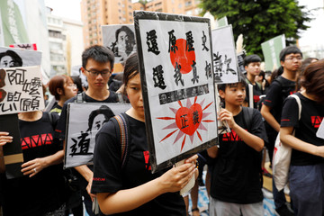"""Protesters hold pictures of """"comfort women"""" and of Japan's Prime Minister Shinzo Abe outside Japan's de facto embassy in Taipei"""