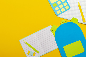 School education papercut background. School bag backpack, notebooks pencils calculator paper cut on yellow background