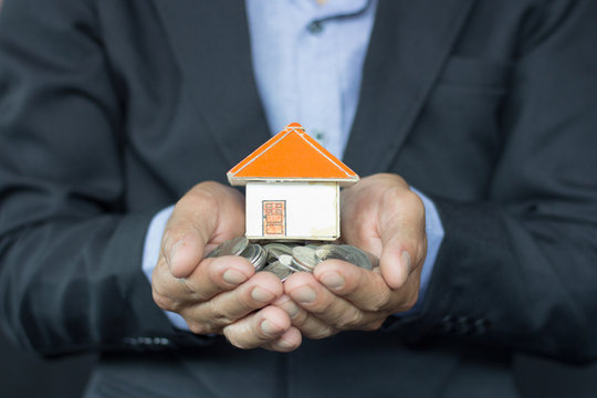 House models and coin in human hands, Mortgage concept by money house from the coins.