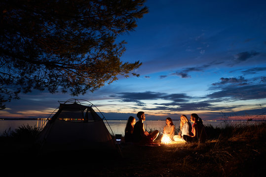 Night summer camping on lake shore. Group of five young tourists sitting on the beach around campfire near tent under beautiful blue evening sky. Tourism, friendship and beauty of nature concept.