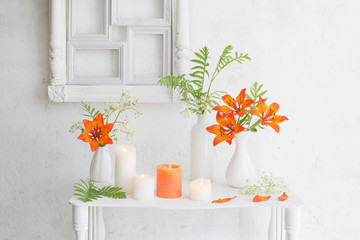 forange flowers and candles on white background