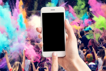 Woman's hands are holding a smartphone with a blank screen and a copy space and in the background a party for young people.