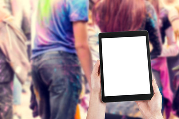 Woman's hands are holding a tablet with a blank screen and a copy space and in the background a party for young people.