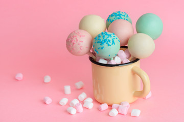 pink, blue, white icing pop cakes and marshmallows in cup over pink background