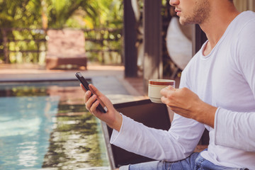 Attractive man using cellphone and drinking coffee while sitting near swimming pool.