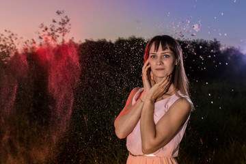 Girl in pink dress outdoors during sunset and cloud of white flour around her