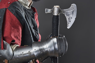 Medieval knight on grey background. Portrait of brutal dirty face warrior with chain mail armour red and black clothes and battle axe