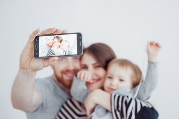 family, holidays, technology and people - smiling mother, father and little girl making selfie with camera over white background