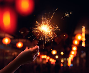 Hand holding a sparkler during Chinese New Year celebration