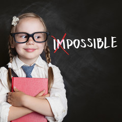 Smart kid with red book and putting a cross over impossible on blackboard background