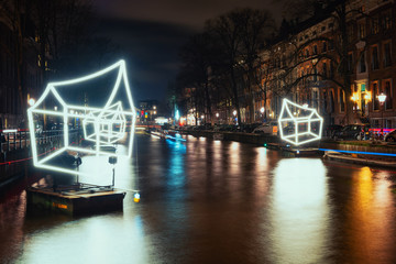 Cottages of light float above the canal during the Festival of Light in Amsterdam
