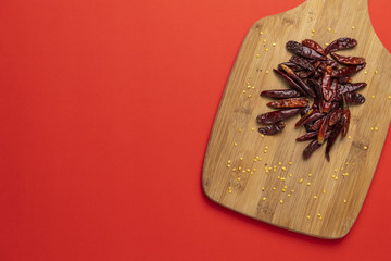 Group of dried asian chilli papers, hot chinese capsicum on the wooden chopping board