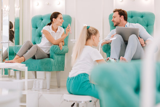 Photo of nails. Dark-haired woman showing photo of nail art her man while having feet massage in beauty salon