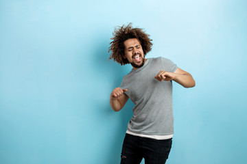 A curly-headed handsome man wearing a gray T-shirt is standing with a cheerful smile and dancing with his eyes closed over the blue background.