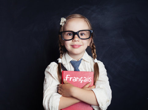 Kid learning french in language school. Happy little girl holding book in her hands on blackboard