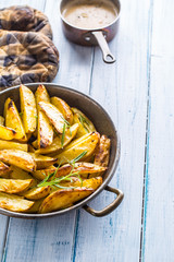 Roasted potatoes in a frying pan on wooden board