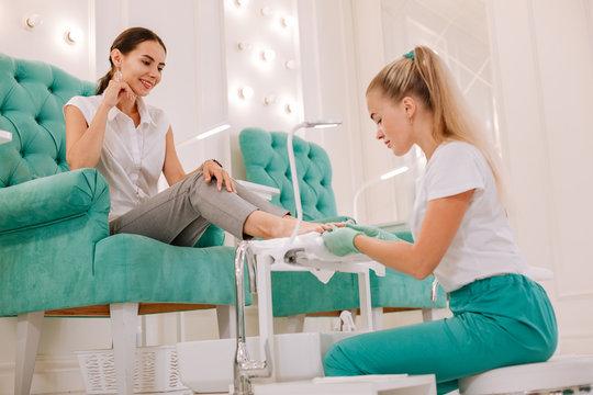 Comfortable armchair. Dark-haired woman feeling relaxed while sitting in comfortable armchair getting pedicure