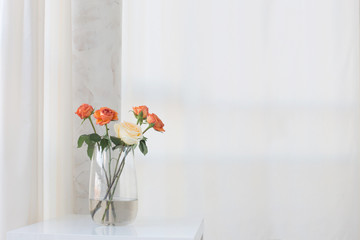 roses in vase on white table