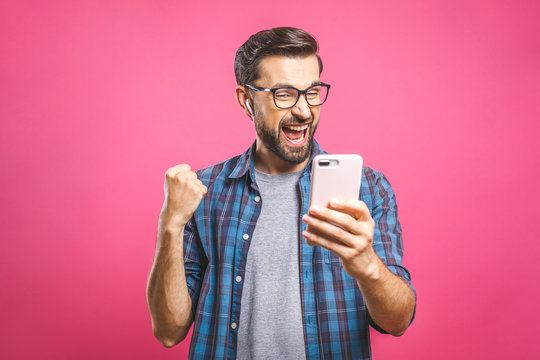 I'm a winner! Happy man holding smartphone and celebrating his success over pink background.