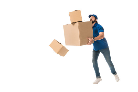 full length view of delivery man holding stacked cardboard boxes falling isolated on white