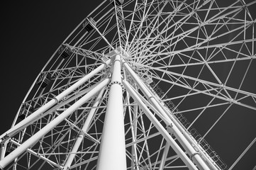 White metal construction of the Ferris wheel on a black sky. Abstraction, city landscape.