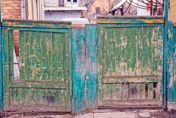 Deurstickers old broken green wooden gate in the street