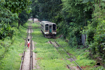 Behind of Myanmarese lady villager walking on the railroad tracks and put the black bag or belongings on the head. Parallel with another rail, the train is running.