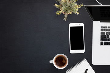 Smart phone and laptop on black office desk with copy space on left side. Blank screen on devices for mockup, app or web site presentation.