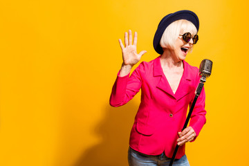 Portrait of charming modern grandmother holds up the microphone