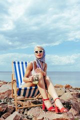 beautiful elegant girl in sunglasses holding jar with cocktail and relaxing in beach chair on rocky shore