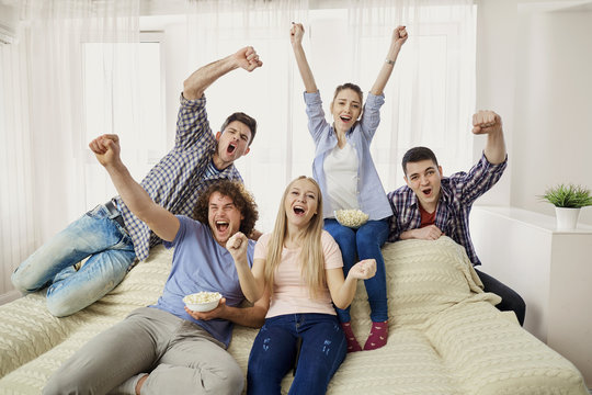 A group of friends of fans watching a sports TV sitting on a sofa in the room.