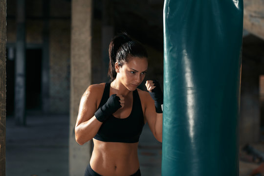 Female boxer punching a boxing bag in warehouse.