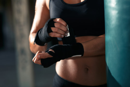 Female boxer bandage her hands before punching a boxing bag in warehouse.