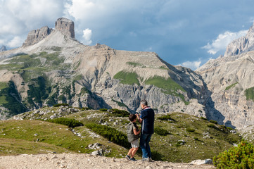 Dad teaching his son to take a picture in the Italian Alps, near the Tre Cime, in the Dolomites, on a summer afternoon.