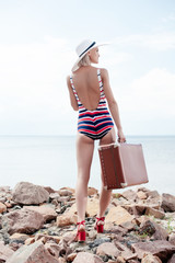 beautiful stylish woman in striped swimsuit and summer hat holding retro suitcase on rocky shore