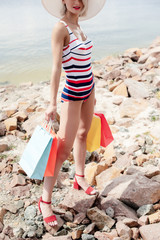 cropped view of beautiful model in striped swimsuit holding shopping bags on rocky beach