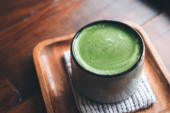A cup of hot matcha latte on wooden floor