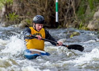 A canoeist paddling through fast running white water - about to go down a drop