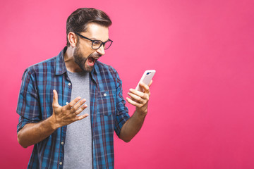 Young caucasian man angry, frustrated and furious with his phone, angry with customer service over pink background. Wall mural