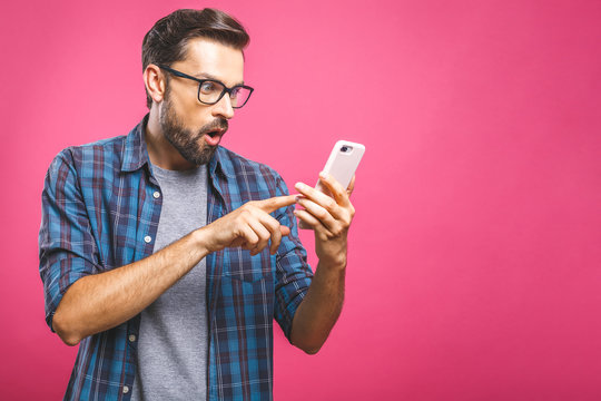 Portrait of a surprised casual man looking at mobile phone isolated over pink background.