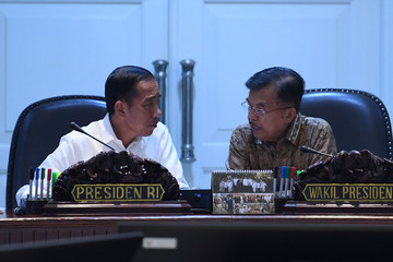 Indonesia President Joko Widodo speaks with Vice President Jusuf Kalla  before the start of a meeting on policy strategies to strengthen foreign exchange reserves at the presidential palace in Jakarta