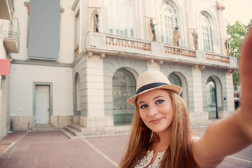 Closeup selfie-portrait of funny attractive girl tourist smiling and taking selfie in the Figueres, Spain, next to the Museum of Salvador Dali. Travel blog. Euro-trip. Cross-processing effect.
