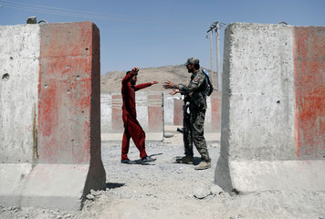 An ANA soldier inspects a passenger at a checkpoint on the Ghazni - Kabul highway