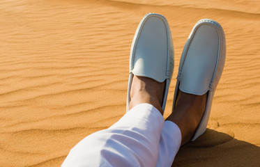 A gentleman's legs crossed in the desert sand. Stylish loafers.