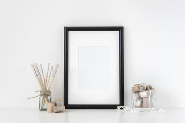 Black a4 frame mockup in interior. Frame mock-Up poster or photo frame and supplies on table, lace and transparent vase, near white wall. Hipster minimalism loft desk space. Background. poster