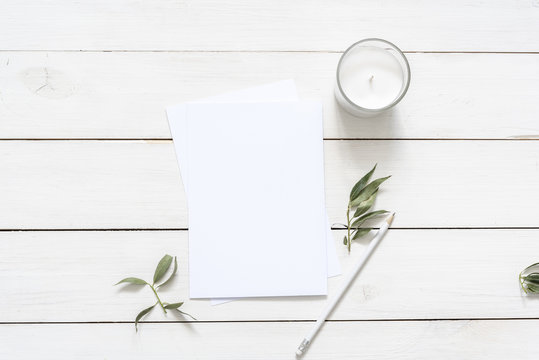 Flat lay with card blank space, stationary, candle, seashells, leaves, white pencil. Ready for you to insert your text, invitation, wedding. Best for social media, backgrounds, headers, blogs, wedding