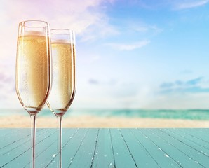 Two glasses of champagne on sea background